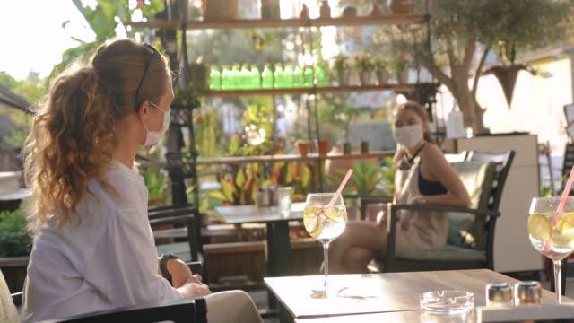 freunde trafen sich in einem café und beobachteten maßnahmen der sozialen distanz. - krankheitsverhinderung stock-videos und b-roll-filmmaterial