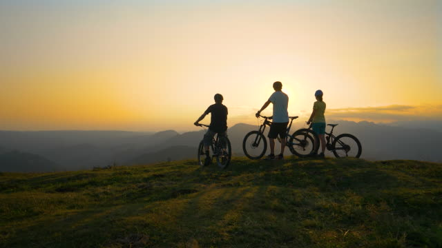 COPY SPACE: Friends observe the sunset after a cross country biking adventure.