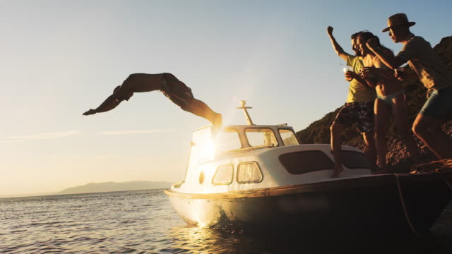 slo mo friends on a boat cheering when a young guy jumps off - tuffarsi video stock e b–roll