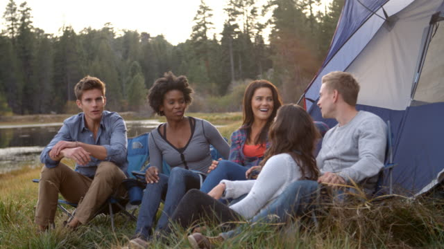 Friends on a camping trip relaxing by their tent near a lake video