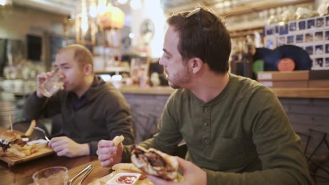 friends on a lunch break - cheeseburger filmów i materiałów b-roll