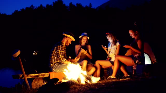 Friends on camping using mobile phones video