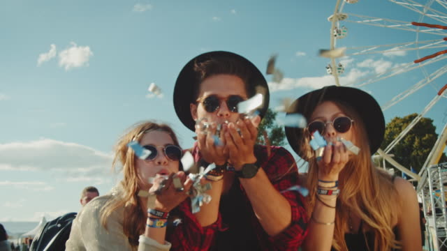 Friends on festival Two girls and a guy are together on a music festival. They throwing some confetti.   carnival celebration event stock videos & royalty-free footage