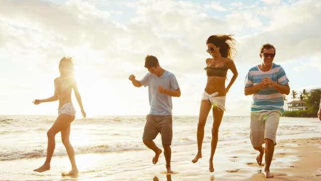 Amigos en la playa al atardecer - vídeo