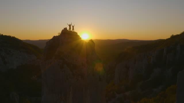 friends on the top of the mountain at sunset - альпинизм стоковые видео и кадры b-roll