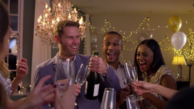 Friends Open Champagne As They Celebrate At Party Together video