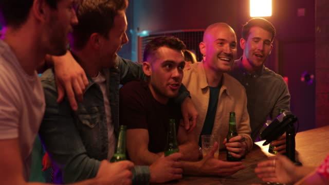 vídeos de stock, filmes e b-roll de amigos, encomendar bebidas - clubbing
