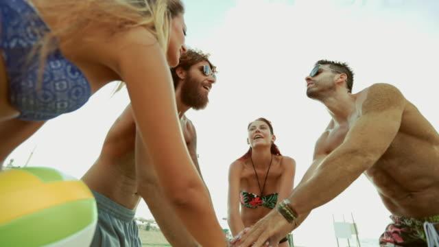 Amigos jugar voley playa y cinco de alto - vídeo