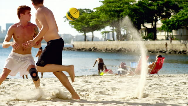 Friends play soccer on the beach in Brazil. video