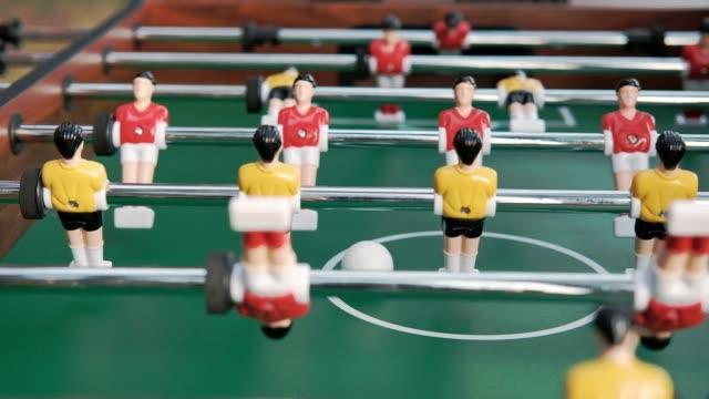 vídeos de stock e filmes b-roll de friends play table football, or kicker. - campeão soccer football azul