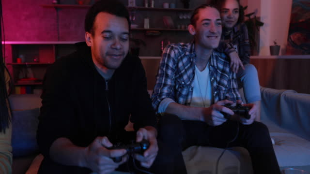 Friends playing video games at home Group of multi ethnic people, friends sitting at home, playing video games. gamer stock videos & royalty-free footage