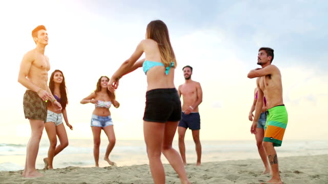 Friends playing volley on the beach Group of friends on the beach, playing together beach volley on the sand at sunset. volleyball sport stock videos & royalty-free footage