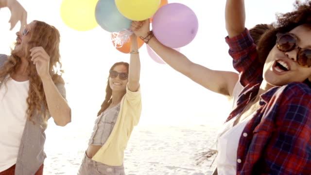 vídeos de stock e filmes b-roll de amigos brincando com balões na praia - mulher balões