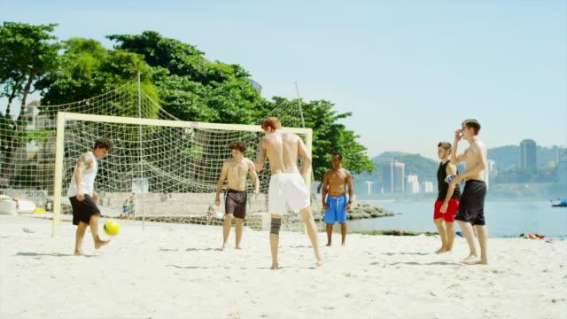 Friends practice soccer skills on a  beach in Brazil video