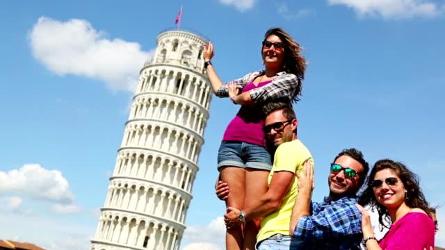 vídeos de stock, filmes e b-roll de amigos empurrando a torre de pisa, em - turista