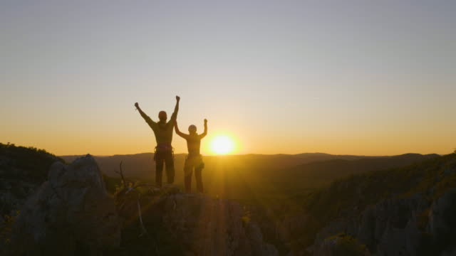 Friends Reaching the Top at Sunset