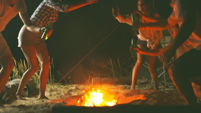 friends relaxing around bonfire - falò spiaggia video stock e b–roll