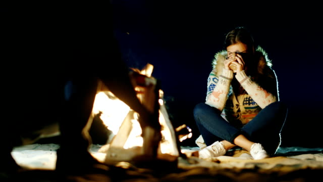 Friends relaxing around the campfire. Woman drinking tea from a cup, a man chopping wood with an ax video