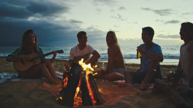 Friends Relaxing at Bonfire Beach Party Group of friends relaxing around bonfire on the beach at sunset bonfire stock videos & royalty-free footage