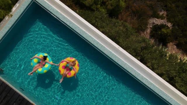 stockvideo's en b-roll-footage met vrienden ontspannen in het zwembad - opblaasband