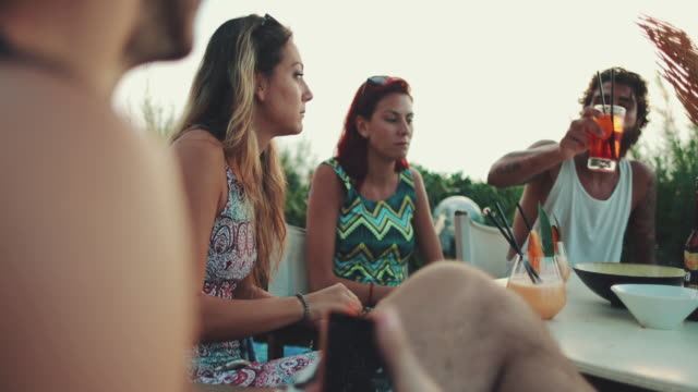 Friends relaxing together during aperitif near the beach Friends relaxing together during aperitif near the beach aperitif stock videos & royalty-free footage