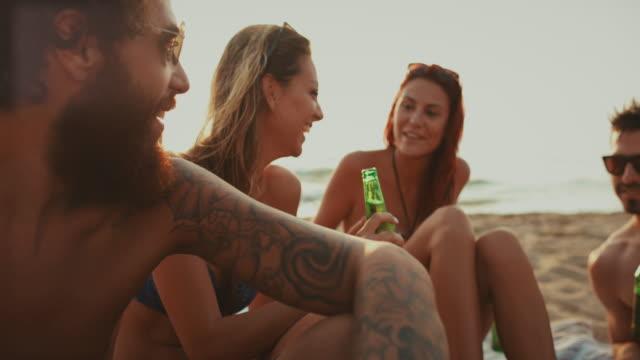 Amigos relax juntos en la playa al atardecer - vídeo