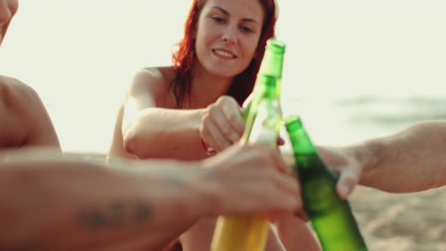 Friends relaxing together on the beach with beers video