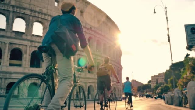 friends riding bicycles in front of colosseum in rome - italian architecture stock videos & royalty-free footage