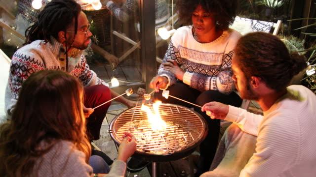vídeos de stock e filmes b-roll de friends roasting marshmallows at back yard - aconchegante