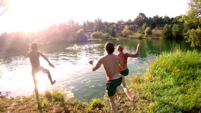 Friends running and jumping into river video