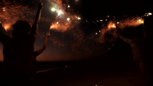 stockvideo's en b-roll-footage met friends running on a beach with fireworks - summer style