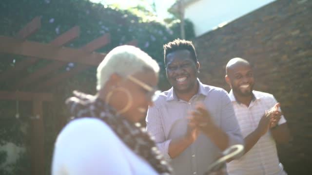 vídeos de stock e filmes b-roll de friends singing and dancing in a garden party - alegria