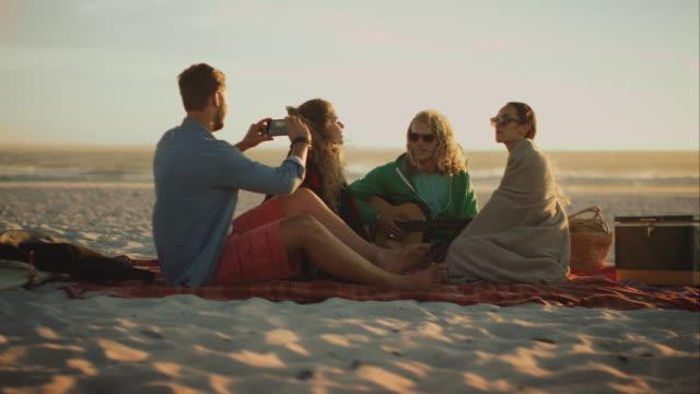 freunde am strand sitzen und relacing - spring break stock-videos und b-roll-filmmaterial