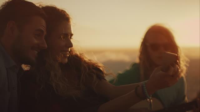 Amici seduti sulla spiaggia e relacing - video