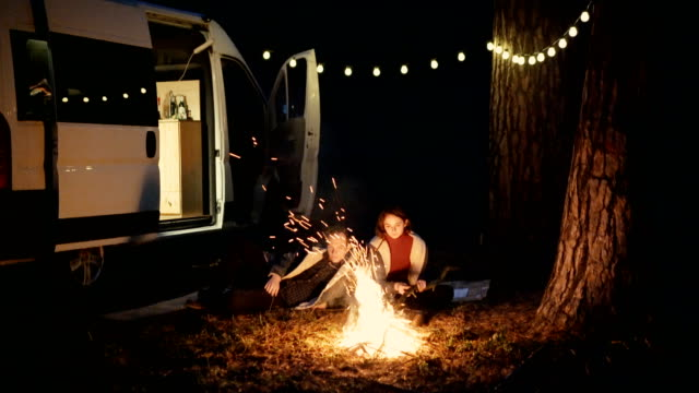 Friends sitting near campfire in the forest near the camper van video