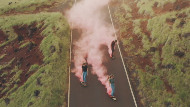 Friends skateboarding at sunset together with colorful smoke video