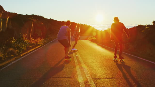 Friends Skateboarding at Sunset Skateboarders riding down hill into the sunset recreational pursuit stock videos & royalty-free footage