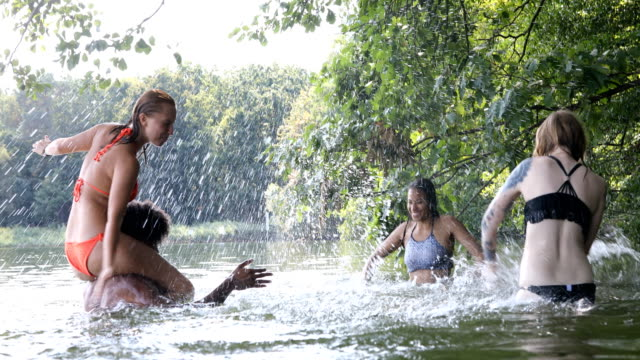Friends splashing water at each other in lake Multi-ethnic friends splashing water at each other. Male is carrying woman on shoulders in lake. They are enjoying summer vacation in forest. locs hairstyle stock videos & royalty-free footage