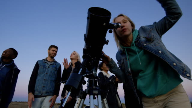 friends stargazing together using a professional telescope - astronomia video stock e b–roll