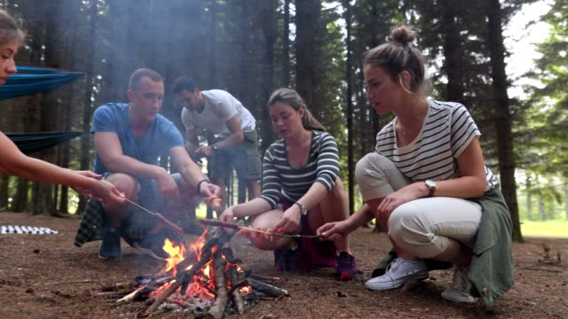 Friends storytelling while cooking lunch on a camp adventure