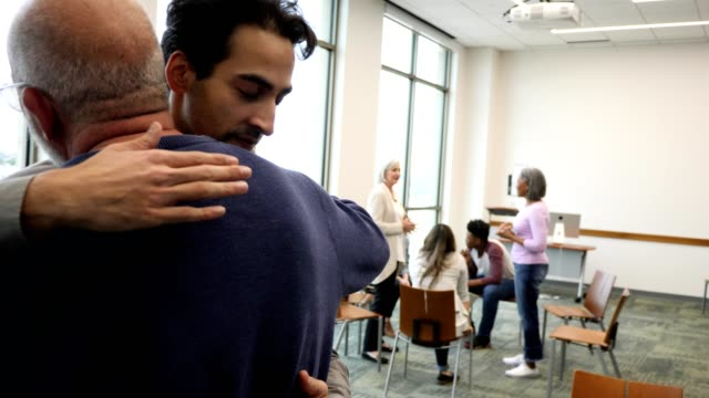 Friends support one another in support group Two male friends embrace before a group therapy or support group meeting. People are preparing to meet in the background. comfort stock videos & royalty-free footage