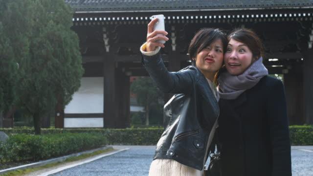 日本のお寺で、selfie を取って友人 - 若者文化点の映像素材/bロール