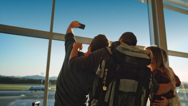 Friends taking a selfie by the glass wall of the sunny airport building Wide handheld shot of friends taking a photo of themselves standing in the glass airport building by the large window overlooking the sunny runway. Shot in Slovenia. 20 29 years stock videos & royalty-free footage
