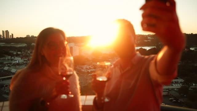 夕暮れ時にセルフを取り、ワインを飲む友人 - 赤ワイン点の映像素材/bロール