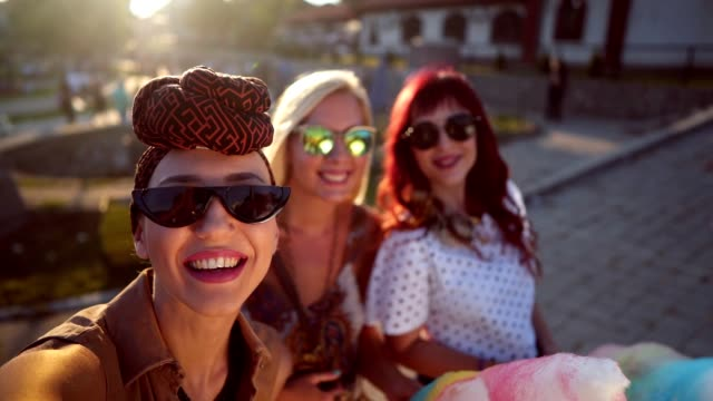 Friends taking selfie in the amusement park Three smiling women are holding cotton candies and taking selfie. cotton candy stock videos & royalty-free footage