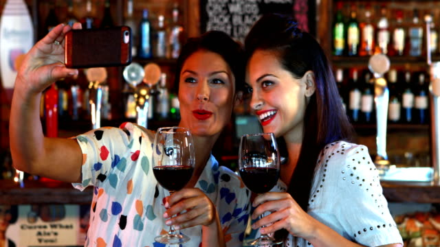 Friends taking selfie on mobile phone while having red wine video