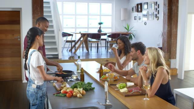 vidéos et rushes de amis parlent aux invités, alors que faire à manger pour les repas de fête - diner entre amis