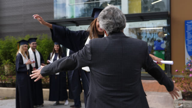 friends talking after graduation ceremony and then woman running to hug her dad to celebrate - tocco accademico video stock e b–roll