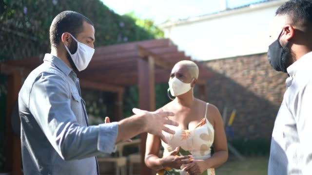 Friends talking using face mask at home