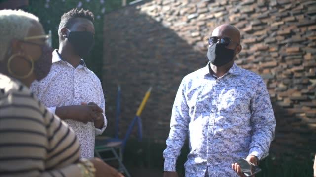 stockvideo's en b-roll-footage met vrienden die gebruikend gezichtsmasker thuis spreken - sociale bijeenkomst